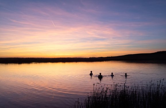 swimmers in sunset lake